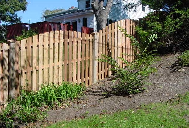 A scalloped Shadowbox partial privacy fence from The Fence Authority, built on a slope.